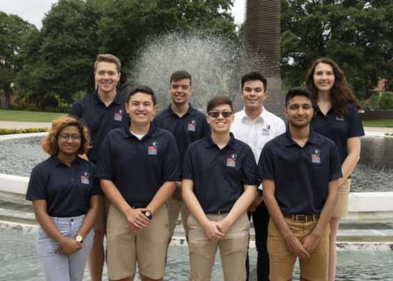 The 9 engineering staff members pose for a formal picture in front of a fountain at Georgia Tech